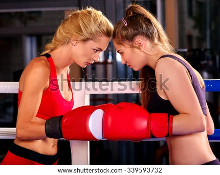 Two  young beautiful women boxer wearing red  gloves to box in ring. - stock photo