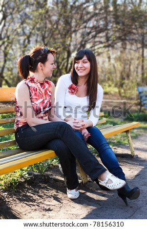Two young beautiful women chatting on a park bench - stock photo