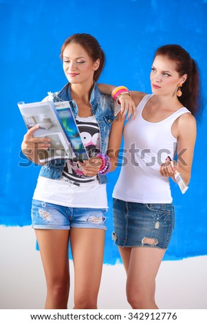Two Young beautiful women holding color palette , standing near wall. - stock photo