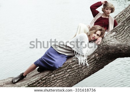 Two young beautiful women posing on a tree, autumn park - stock photo