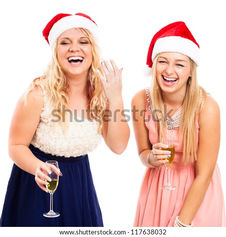 Two young blond laughing women celebrating in Christmas hat, isolated on white background. - stock photo