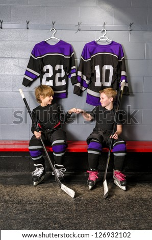 Two young boys fist pump before hockey game in dressing room - stock photo