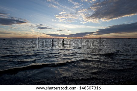 Two young boys going for a night swim in the ocean - stock photo