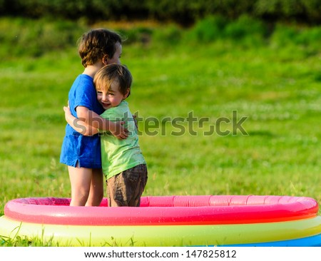 Two young boys hugging each other in a paddling pool in summer