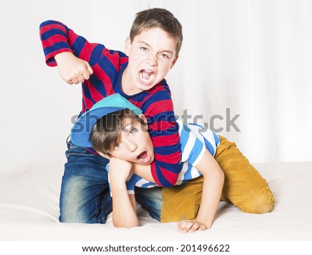 two young boys in bed and fighting - stock photo