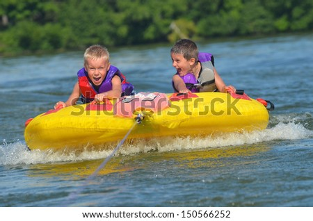 two young boys laughing while on a tube behind a boat - stock photo