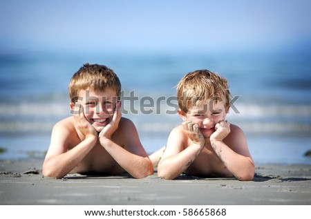 two young boys laying on a sandy beach - stock photo