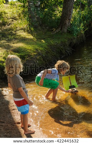 Two young boys play with a homemade sailing boat in the shallow water at the shore line, They're on a beach, with grass, bushes and trees in the background. It is summertime. - stock photo