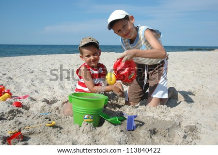 two young boys playing on the beach - stock photo