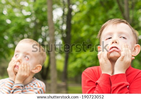 Two young boys playing outdoors together in a park or garden standing pulling funny faces using their hands to pull down on their cheeks distorting their features - stock photo