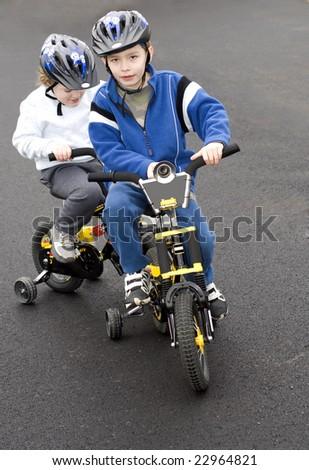 Two young boys riding bicycles wearing helmets - stock photo