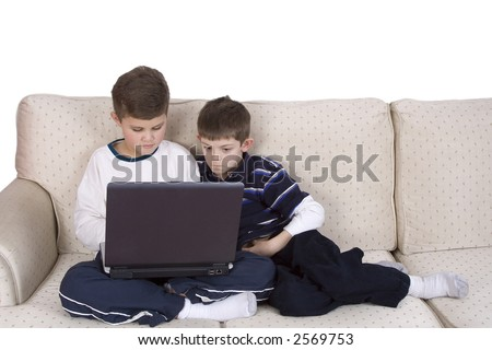 Two young boys sitting on a couch looking at a laptop. Serious expressions on their faces an a white background.
