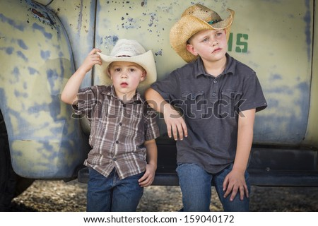 Two Young Boys Wearing Cowboy Hats Leaning Against an Antique Truck in a Rustic Country Setting.  - stock photo