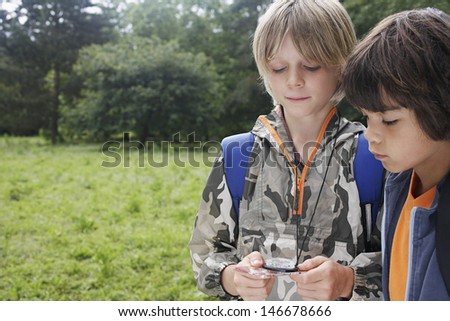 Two young boys with backpacks using compass - stock photo