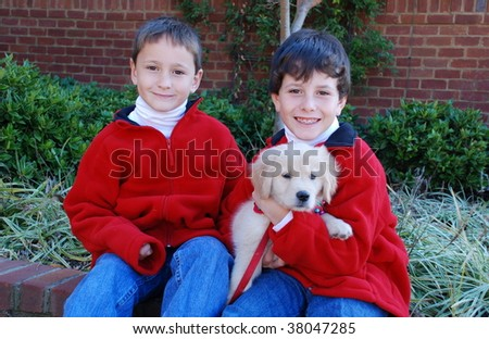 Two young boys with their Christmas golden retriever puppy. - stock photo