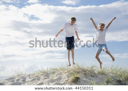 two young brothers at the beach - stock photo
