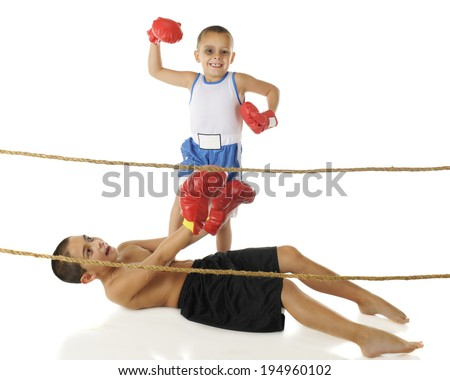 Two young brothers boxing behind ropes.  The preschooler (with a shiner) stands in victory with his foot on his big brother's chest, while the older one attempts to get up.  On a white background. - stock photo