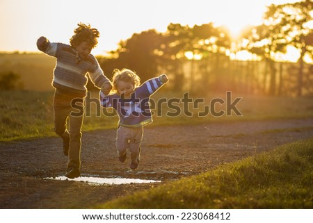 two young brothers holding hands and jumping over a puddle at sunset - stock photo