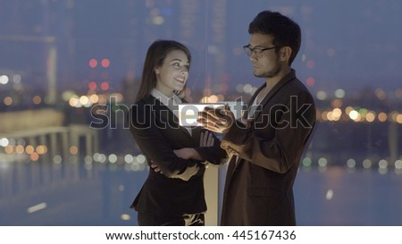 two young business coworkers looking at tablet computer screen talking together. asian man having a conversation with a caucasian women. professionals meeting scene  - stock photo