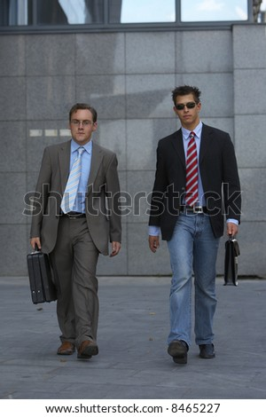Two young business men are heading up to a meeting