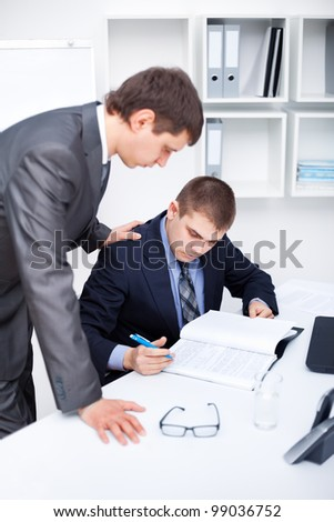 Two young business men signing papers at office - stock photo