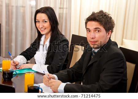 Two young business people having meeting and sitting on chairs at table - stock photo
