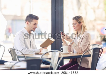 Two young business people on a coffee break in a restaurant. - stock photo
