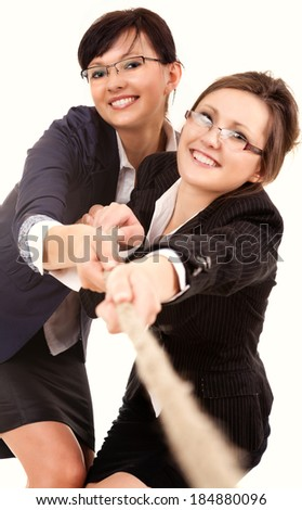 two young business woman, pulling the rope, white background - stock photo