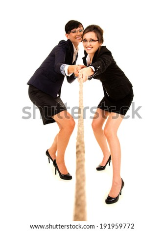 two young business woman, pulling the rope, white background, full lenght - stock photo