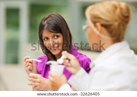 two young business women eating yogurt outdoors