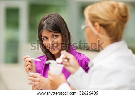two young business women eating yogurt outdoors - stock photo