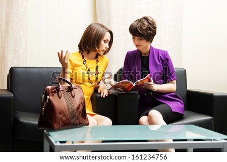 Two young business women sitting on the couch in showroom - stock photo