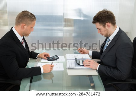Two Young Businessman Calculating Bills Using Calculator At Workplace - stock photo