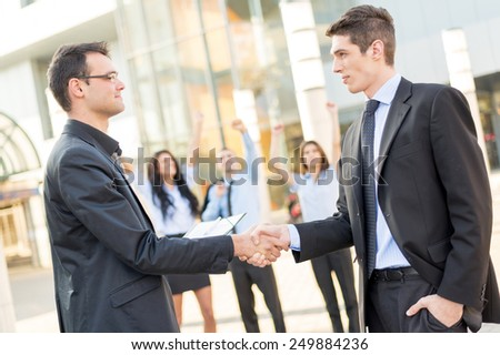Two young businessman in front of office building shaking hands, while in the background there is a small group of business people hands raised celebrate the deal.