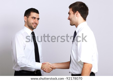 Two young businessman in white shirt makes a handshake - stock photo
