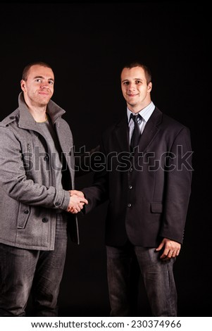 Two young businessman shaking hands - stock photo