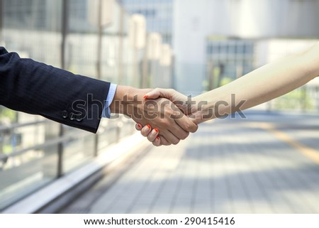 Two young businessman shaking hands in street - stock photo