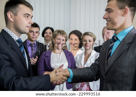 Two young businessmen congratulates each other while smiling corporate team applauds them on the background  - stock photo