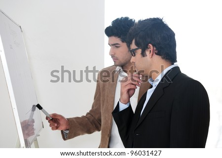 two young businessmen discussing business strategy in a meeting, Indian business man with latin american colleague, two serious businessmen, - stock photo