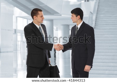 Two young businessmen greet in business center collage - stock photo