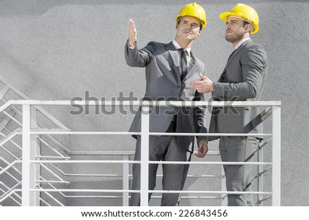 Two young businessmen in hard hats discussing on stairway - stock photo