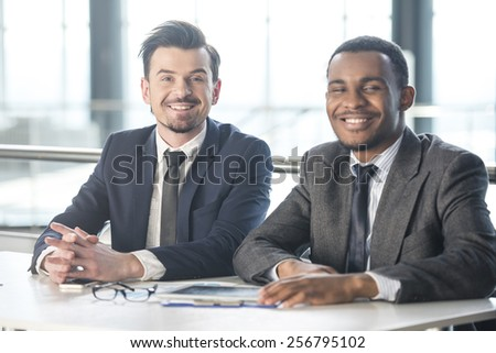 Two young businessmen in the modern office at work. - stock photo