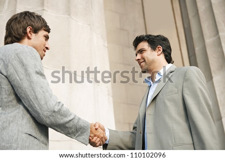 Two young businessmen shaking hands in agreement while standing next to a large building's column, smiling. - stock photo