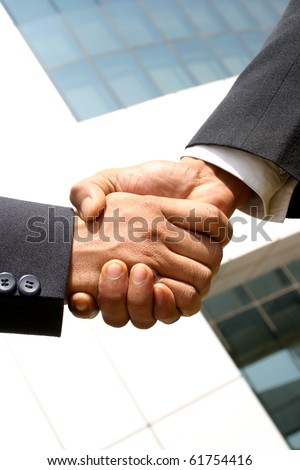 Two young businessmen shaking hands in front of a building. - stock photo