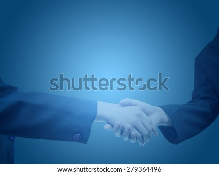 two young businessmen shaking hands on blue background. concept for business and success - stock photo