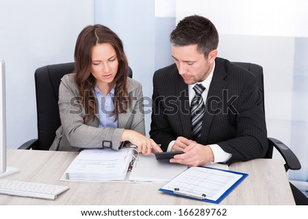 Two Young Businesspeople Calculating Bills At Desk In Office