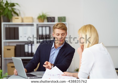 Two young businesspeople discussing a document as they sit working together as a team at a table in the office with the man pointing to the paperwork - stock photo