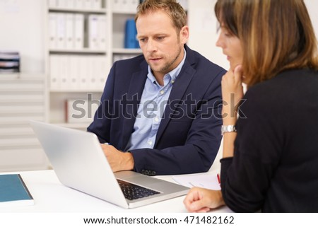 Two young businesspeople having a meeting sharing a laptop computer together at a table in the office as they study information on the screen