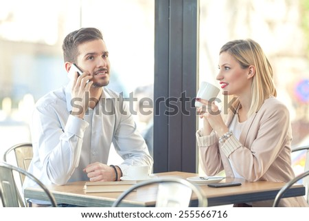 Two young businesspeople on coffee break in a cafe. Young man talking on mobile phone and young woman drinking tea. - stock photo