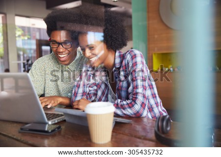 Two Young Businesspeople Working On Laptop In Coffee Shop - stock photo